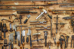 The tools of a tanner for working with leather on the wall in a tannery. Royalty Free Stock Image