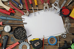 Tools on a timber floor, the top view. Tools are spread out on a timber floor round a notebook for records, the top view Stock Photography