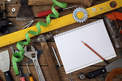 Tools on a timber floor, the top view. Tools are spread out on a timber floor round a notebook for records, the top view Stock Image