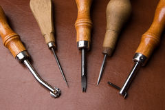 Tools to work leather. Some tools to work leather over leather background Royalty Free Stock Photography