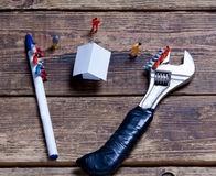 Tools, toy people and paper Royalty Free Stock Photo