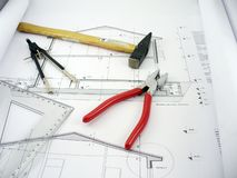 Tools of trade. Construction site with blueprints,hammer,clamp and compass Royalty Free Stock Photos