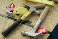 Tools of the Trade. Three hammers, a ruler, and chalk line on plywood Royalty Free Stock Photography