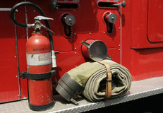 Tools of the Trade. Fire extinguisher and hose on the side of a red fire truck Stock Photography