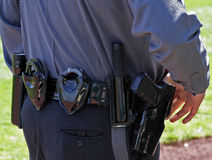 Tools of the Trade. Close-up of police officer's belt, including gun, handcuffs, baton and flashlight royalty free stock images