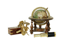 Tools for travel. Brass Sextant used for navigating by the stars, telescoping telescope used to see distances, Old world globe with basic navigation notations Stock Image