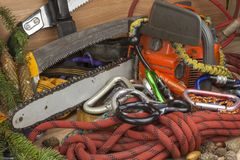 Tools for trimming trees, utility arborists. Chainsaw, rope and carabiners to work lumberjack Royalty Free Stock Photography