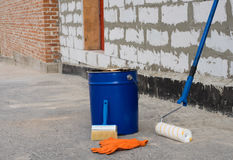 Tools for waterproofing. Mittens, roller, ceiling brushes and a bucket of bitumen primer stock photo