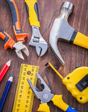 Tools on wooden board hammer nippers pliers wrench Royalty Free Stock Photo