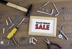 Tools on a wooden table and a wooden frame with text Black Frida Royalty Free Stock Photography