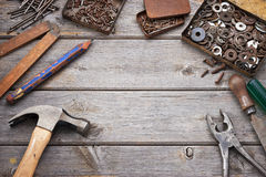 Tools Workbench Wood Background. A tools workbench with, pencil, hammer, nails and screws in old tin boxes Stock Photography