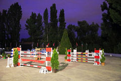 Toon het springen hindernissen op de rascursus bij avond Stock Foto