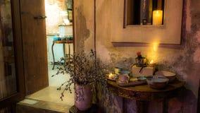 Toon a-reeks antieke koppen op een houten lijst over honderd jaar oud met grijze muren Ingang aan de winkel stock foto