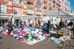 Toont de kleding van de verkoop tweede hand op dagelijkse Vlooienmarkt op Waterlooplein (Waterloo Vierkant), handelaars hun bric- Stock Afbeeldingen