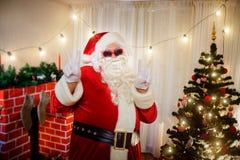 Toont de positieve rode glazen van Santa Claus een gebaar van vrede, overwinning in de ruimte bij Kerstmis royalty-vrije stock foto's
