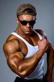 Toont de sterke atletische mens van de bodybuilder spierwapen Royalty-vrije Stock Foto