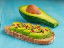 Toost en gesneden avocado en de helft van het fruit stock foto