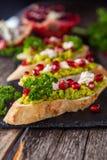 Toost met avocado en granaatappel op houten lijst Stock Foto's