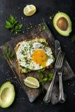 Toost met avocado, spinazie en gebraden ei op houten scherpe beer Stock Foto's