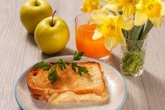 Toost met boter en kaas op witte plaat, twee appelen, glas o stock foto