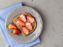 Toost met chocolade en aardbei, Enige sandwich met chocoladekaas op witte plaat, hoogste mening stock foto