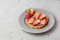 Toost met chocolade en aardbei, Enige sandwich met chocoladekaas op witte plaat, hoogste mening stock afbeelding