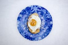 Toost met gebraden eieren op een blauwe Kerstmisplaat stock foto