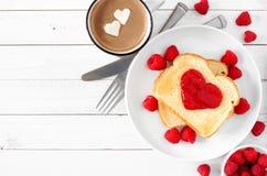 Toost met jam in vorm van hart, hete chocolade en frambozen, hoogste mening over wit hout stock afbeeldingen