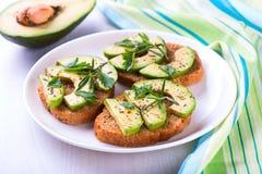 Toost met roggebrood, avocado en kruiden op witte plaat Royalty-vrije Stock Foto