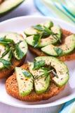 Toost met roggebrood, avocado en kruiden op witte plaat Stock Foto