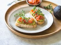 Toosts met avocado en gezouten zalm met verse erwtenspruiten op een plaat op een houten dienblad stock afbeeldingen