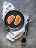 Toosts met avocado en gezouten zalm en zwarte sesamzaden op een zwarte plaat op een grijze achtergrond stock fotografie