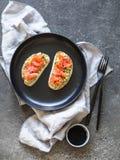 Toosts met avocado en gezouten zalm en zwarte sesamzaden op een zwarte plaat op een grijze achtergrond royalty-vrije stock foto's