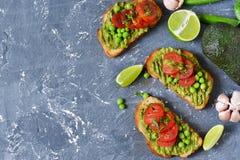 Toosts met avocado, groene erwten en tomaten royalty-vrije stock afbeelding