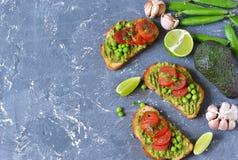 Toosts met avocado, groene erwten en tomaten royalty-vrije stock foto's