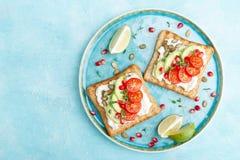 Toosts met feta-kaas, tomaten, avocado, granaatappel, pompoenzaden en lijnzaadspruiten Heerlijk en gezond dieetontbijt stock fotografie