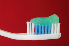 Tooth Brush. A closeup of a tooth brush with toothpaste on a red background Stock Image