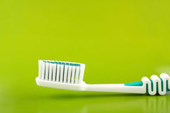 Tooth-brush. White-green tooth-brush close on a green background Stock Photography