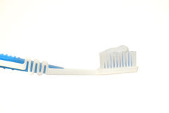 Tooth brush and paste. White and blue tooth brush with tooth paste on it, isolated on white background, shot from the side Royalty Free Stock Photos