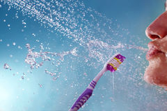 Tooth brush under the shower. Young female under the shower with the tooth brush Stock Photo