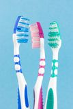 Tooth-brushes. Three colored tooth-brushes on blue background Royalty Free Stock Images