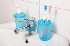 Tooth brushes and soap on white sink Royalty Free Stock Image