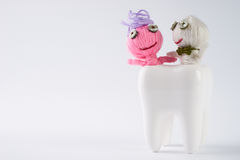 Tooth with cute dolls attacked by bacteria on isolate white. Background with copy space. Dental caries concept Stock Image