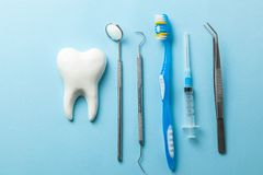 Tooth and dental instruments on blue background. Dental treatment. Dentist tools mirror, hook, tweezers, syringe and toothbrush.  royalty free stock photography