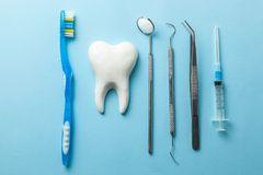 Tooth and dental instruments on blue background. Dental treatment. Dentist tools mirror, hook, tweezers, syringe and toothbrush.  royalty free stock photo