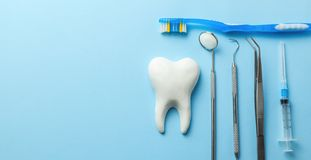 Tooth and dental instruments on blue background. Dental treatment. Dentist tools mirror, hook, tweezers, syringe and toothbrush. Copy space for text stock image
