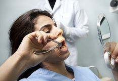 Tooth extracting. A patient is trying to extract her own tooth as the doctor is standing behind her Royalty Free Stock Images