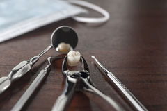 Tooth extraction concept. With an array of stainless steel dental tools and a mask with the extracted tooth clasped in the pincers and reflected in the mirror Stock Photography