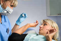 Tooth extraction. Dentist at work, tooth extraction, female patient feared by forceps Stock Images