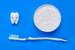 The tooth figurine smiles next to the tooth powder and toothbrush. The view from the top. Flat lay. royalty free stock photography